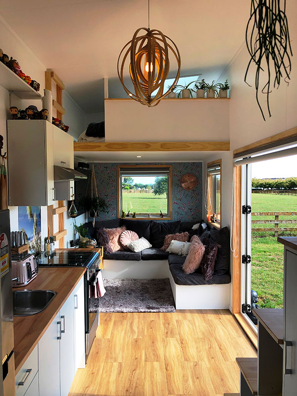 Inside a Tiny House showing living room, kitchen and pendent lamp