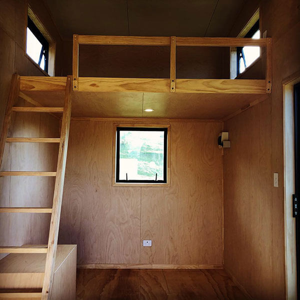 ply lined cabin showing stairs ladder and mezzanine level